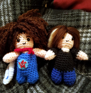 One curly-haired and one straight-haired small amigurumi side by side
